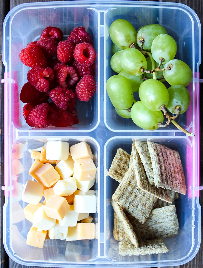 Cheese and crackers, green grapes, and raspberries are plated in a lunch box.