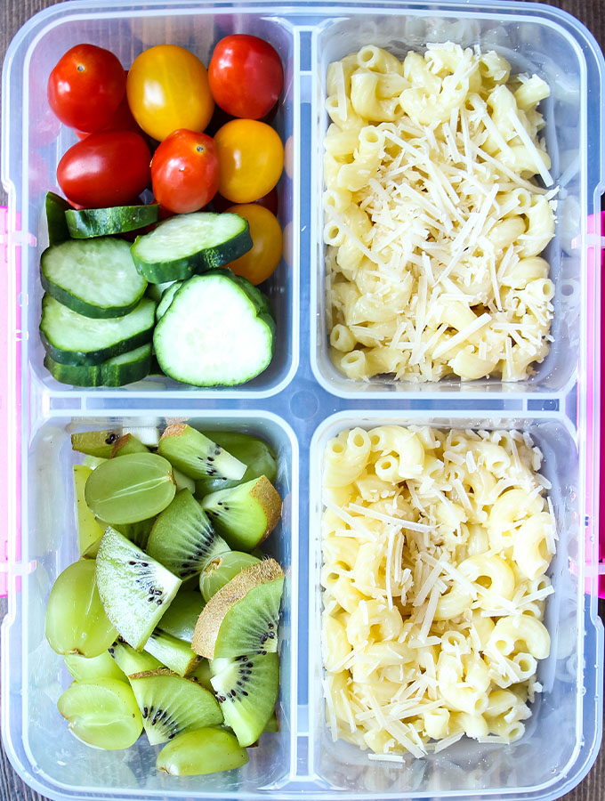 Buttered pasta, kiwi and green grapes, and tomatoes and cucumbers are plated in a lunch box.