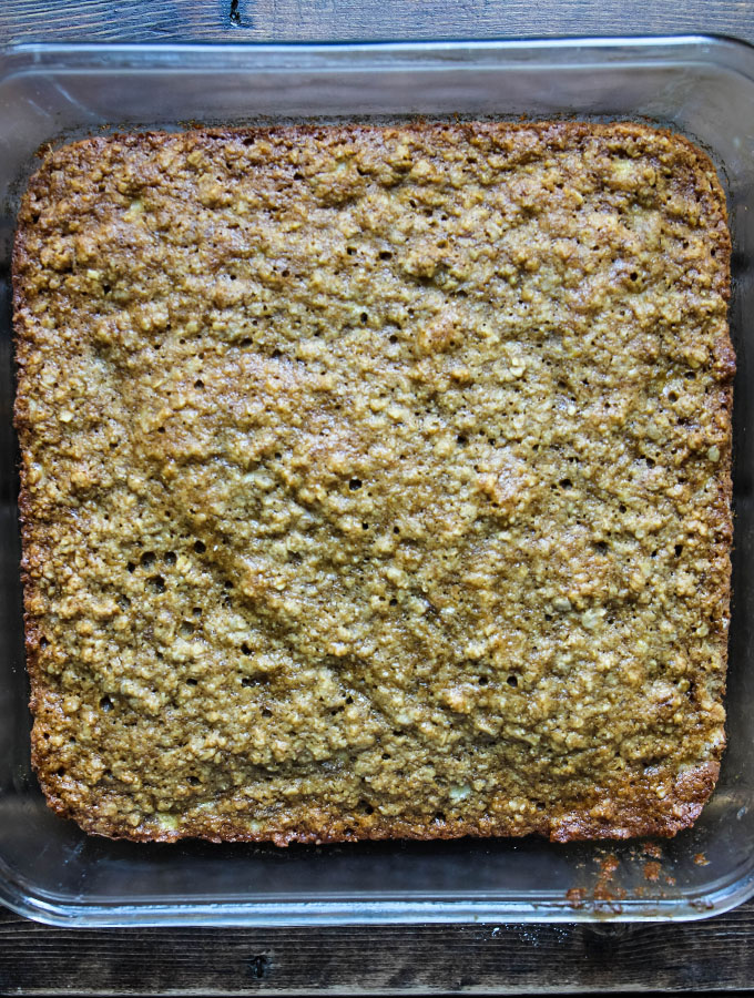 Banana oatmeal bars are baked in a glass pan until the edges are golden brown.
