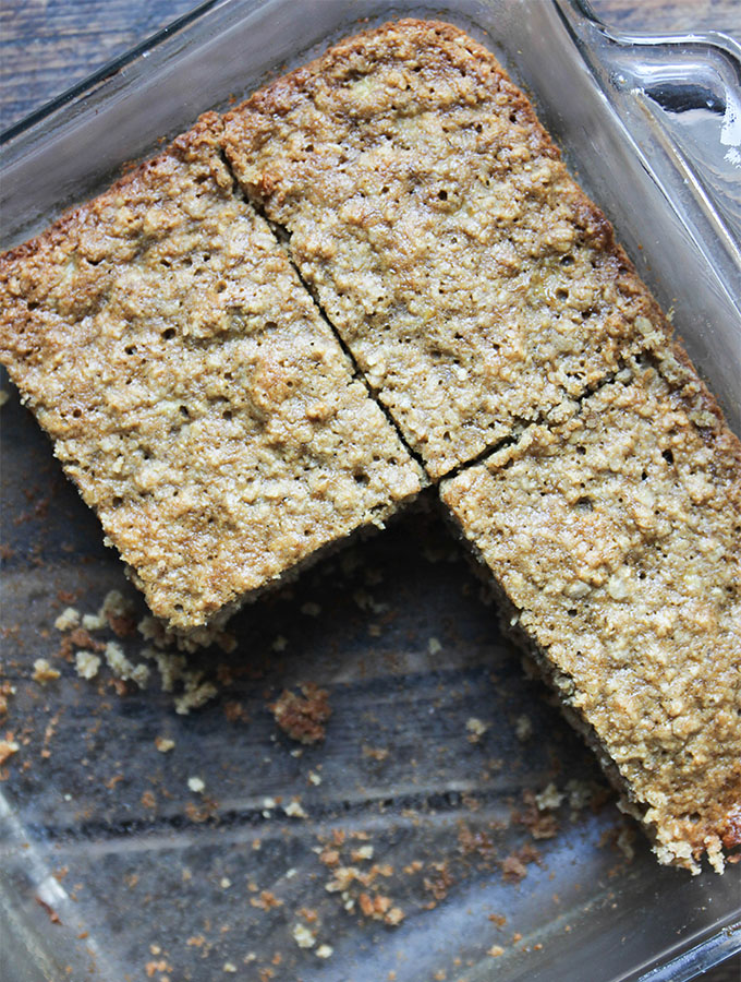 The banana oatmeal bars are sliced in the glass pan and a few are removed.