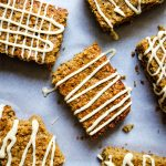 The banana oatmeal breakfast bars are drizzled with maple cream cheese frosting on parchment paper.