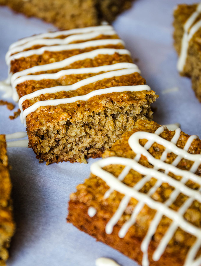 The banana oatmeal bars are drizzled with maple cream cheese frosting on top of parchment paper.