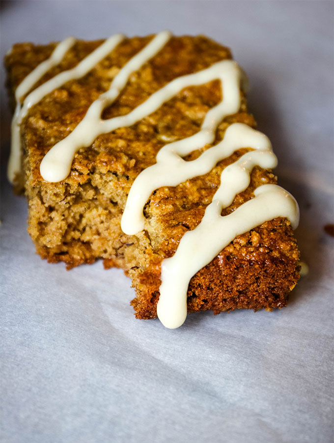 A big bite is taken out of teh breakfast bars and is drizzled with maple cream cheese frosting.