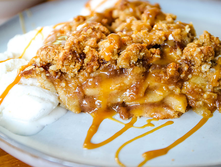 A slice of Dutch apple pie is plated and drizzled with caramel.