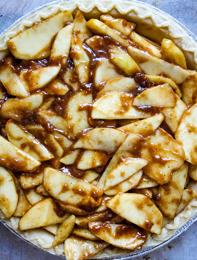 Apple sliced are tossed with cinnamon, butter, and sugar before it's placed in the pie crust.