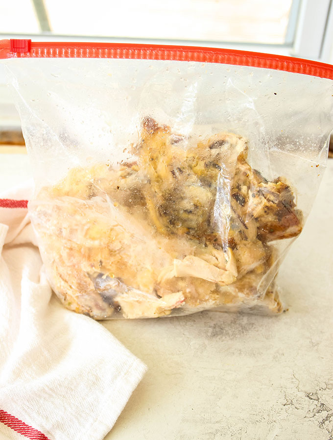 Chicken bones are collected in a freezer safe plastic bag so they can be used for broth at a later time.