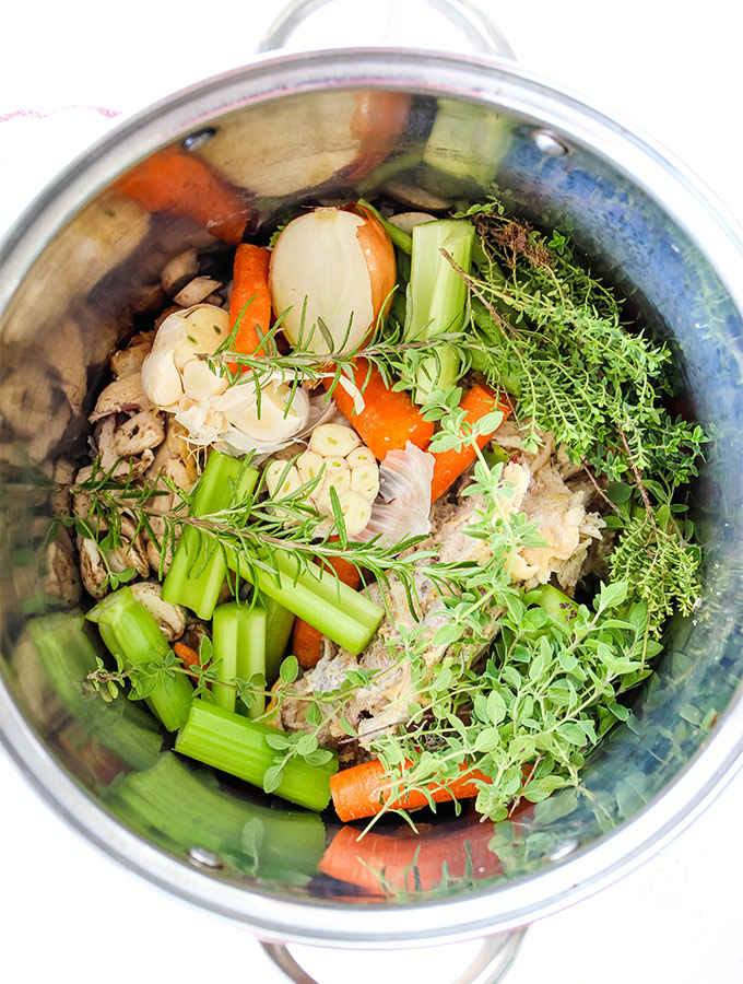 Chicken, herbs, vegetables, and a few other ingredients are combined in a stockpot to make a flavorful bone broth.