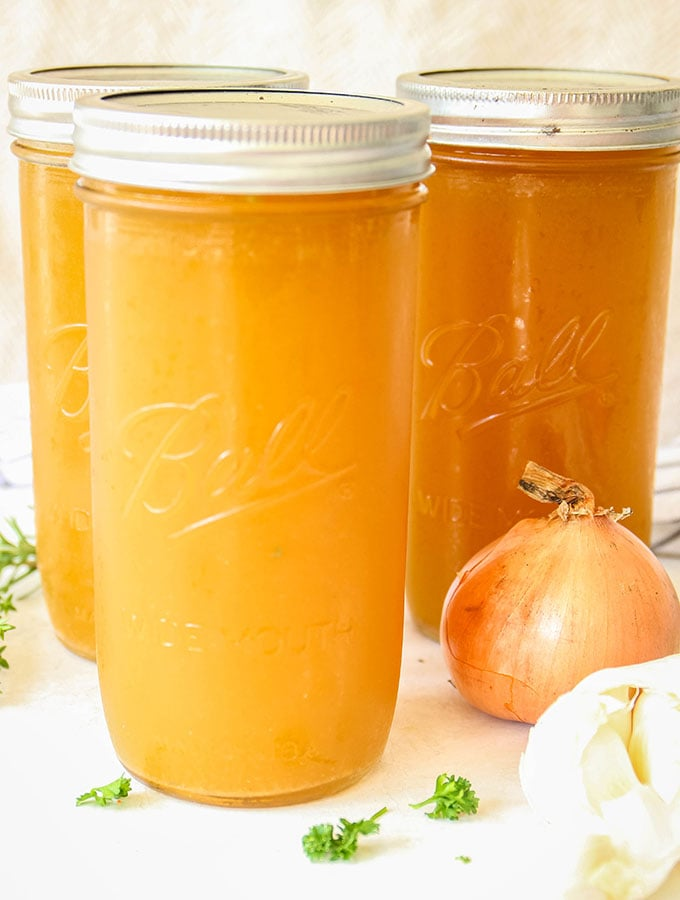 Chicken bone broth is poured into a few glass jars and topped with a lid before they are frozen.