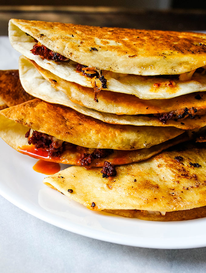 Chorizo and shrimp quesadillas are piled on top of eachother on a white plate.