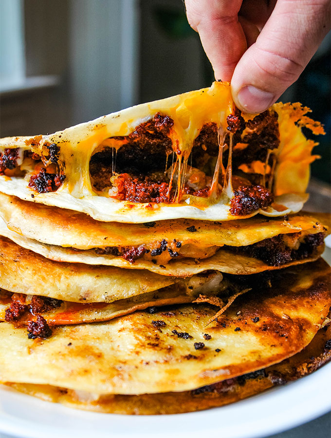 A hand is lifting a half of the tortilla to show the cheesy inside of the quesadilla.