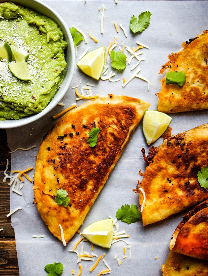 Margarita guacamole is plated next to the quesadillas and topped with cheese and limes.