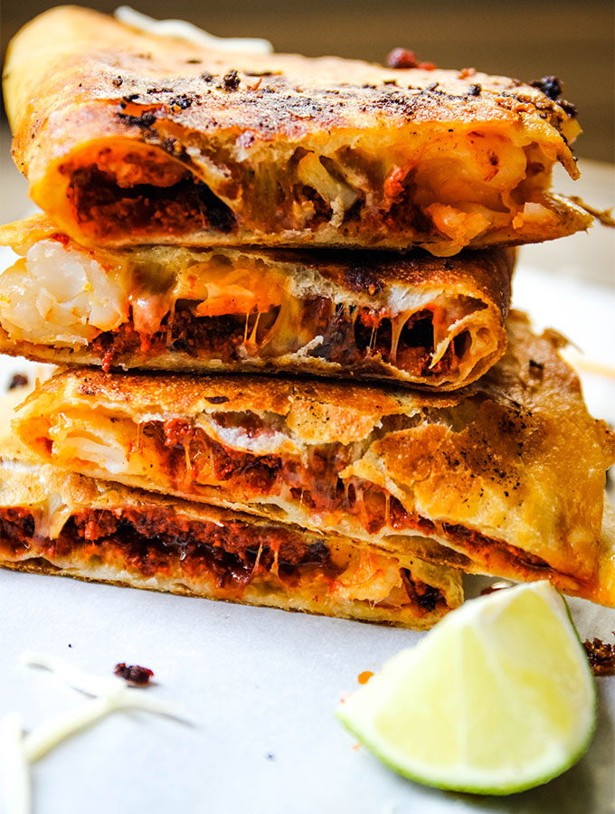 The chorizo and shrimp quesadillas are cut in half and stacked on parchment paper.