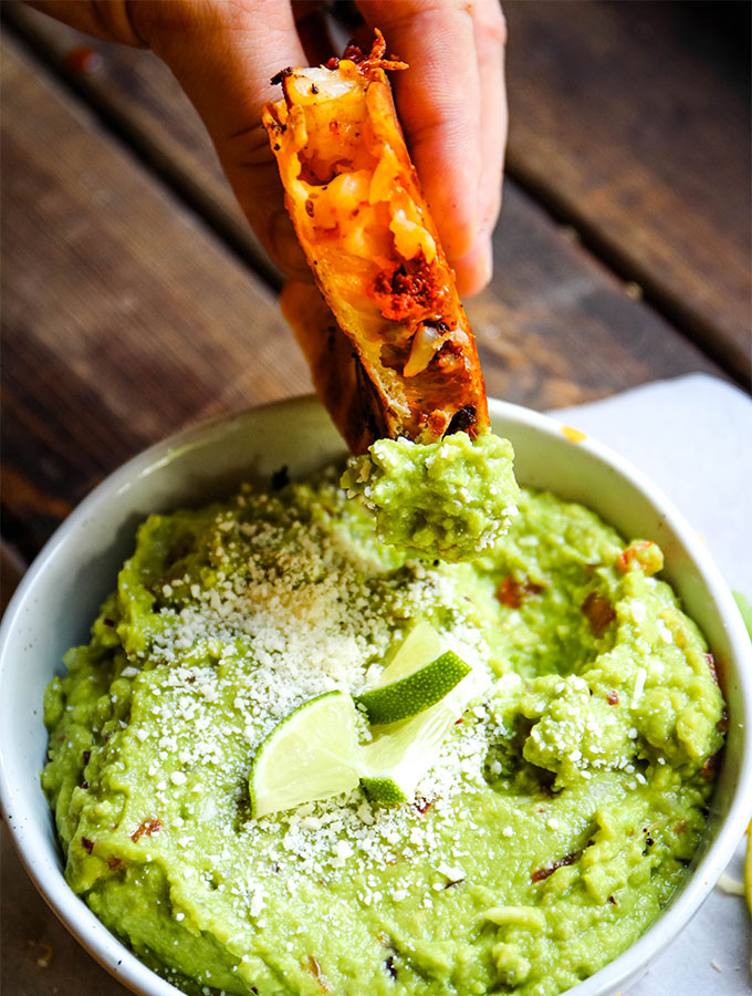 A hand is dipping the chorizo sausage quesadilla into the margarita guacamole.