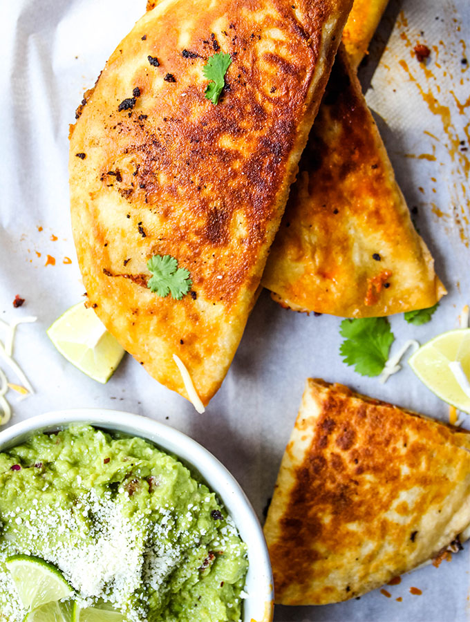 The chorizo sausage quesadillas are stacked on parchment paper next to a bowl of margarita guacamole.