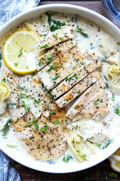 Juicy seared chicken breasts are plated in a white bowl and topped with sauce, cracked pepper, lemons and parsley.