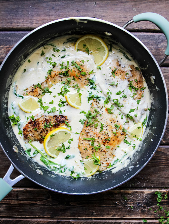Creamy Spinach and Artichoke Chicken Skillet is cooked in one pan and topped with parsley and lemon wedges.