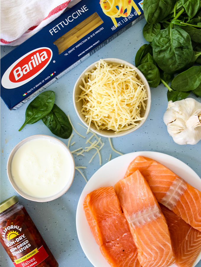 The creamy Tuscan salmon and pasta ingredients are displayed individually on a baking sheet.