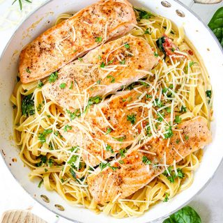 Salmon is placed on top of the pasta and topped with parmesan cheese and fresh chopped parsley.
