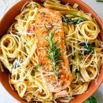 A sprig of fresh rosemary is placed on top of the pan seared salmon and creamy pasta.