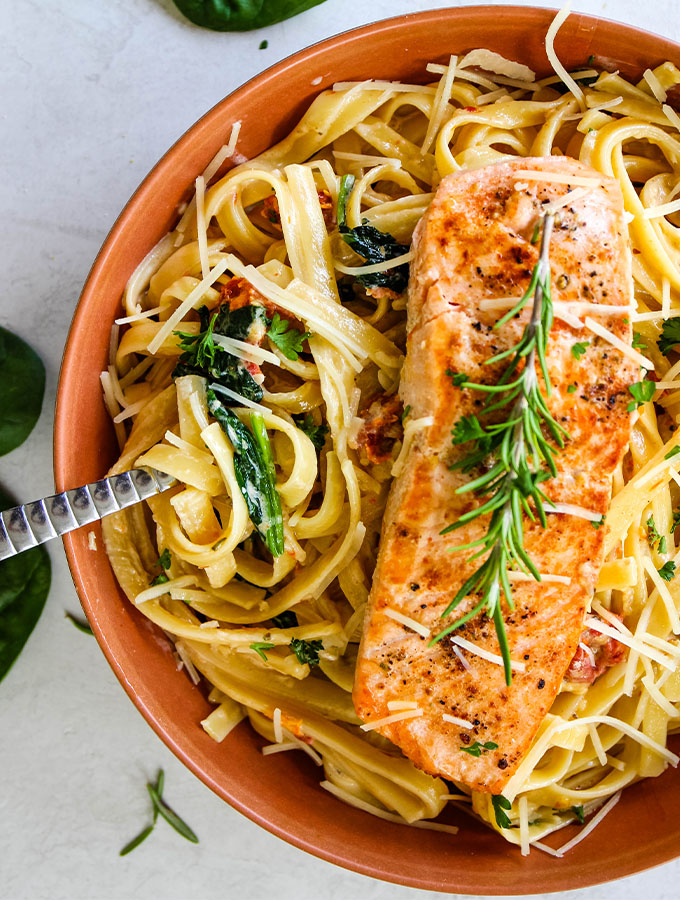 A fresh sprig of rosemary is placed on top of the salmon filet and pasta, then parmesan cheese is sprinkled.