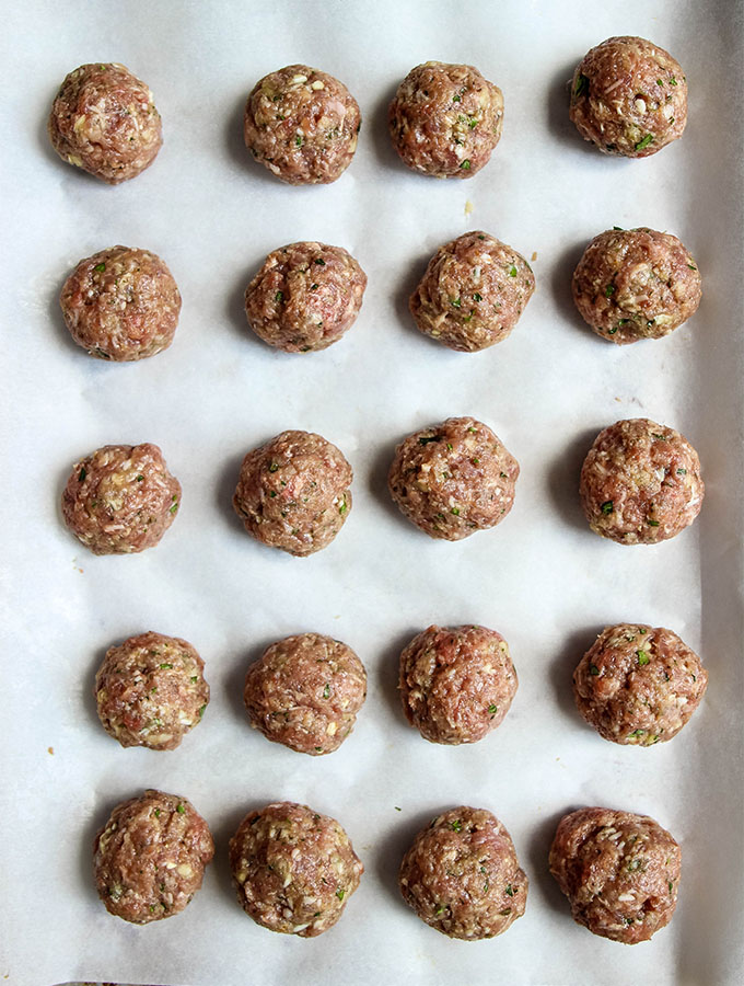 Raw meatballs are lined on a parchment paper lined baking sheet before the are placed in the oven.