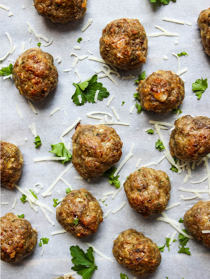 Italian meatballs are baked on a parchment paper lined baking sheet and topped with fresh parsley and parmesan cheese.