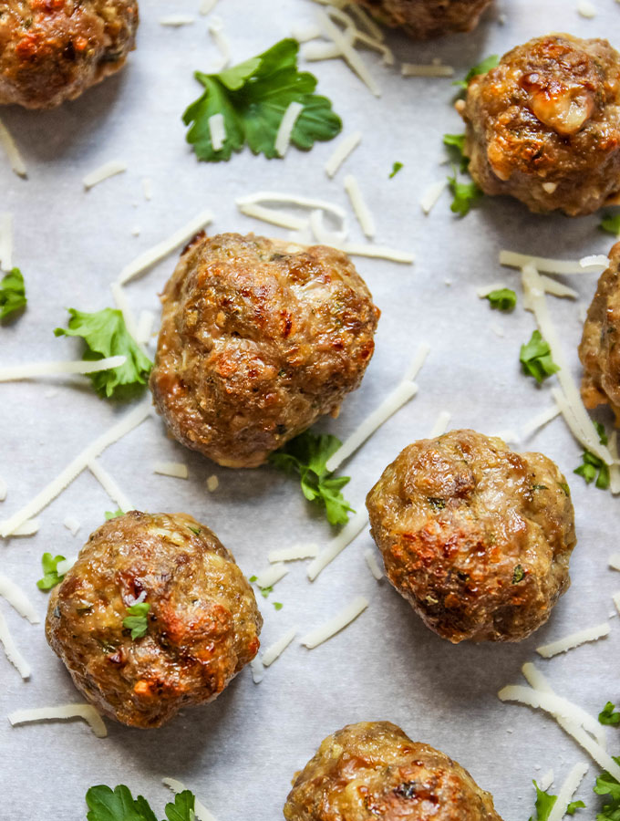 Italian meatballs are baked on a parchment paper lined baking sheet and topped with garnishes like parsley and cheese.