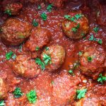 Italian meatballs are simmered in tomato sauce and topped with fresh parsley for garnish.
