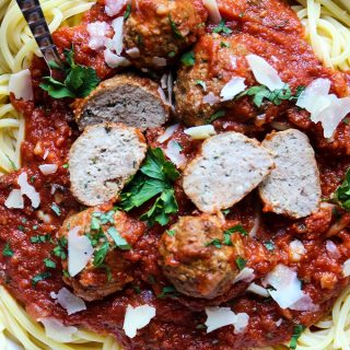 Italian meatballs are sliced in half on top of spaghetti pasta to show tender texture.
