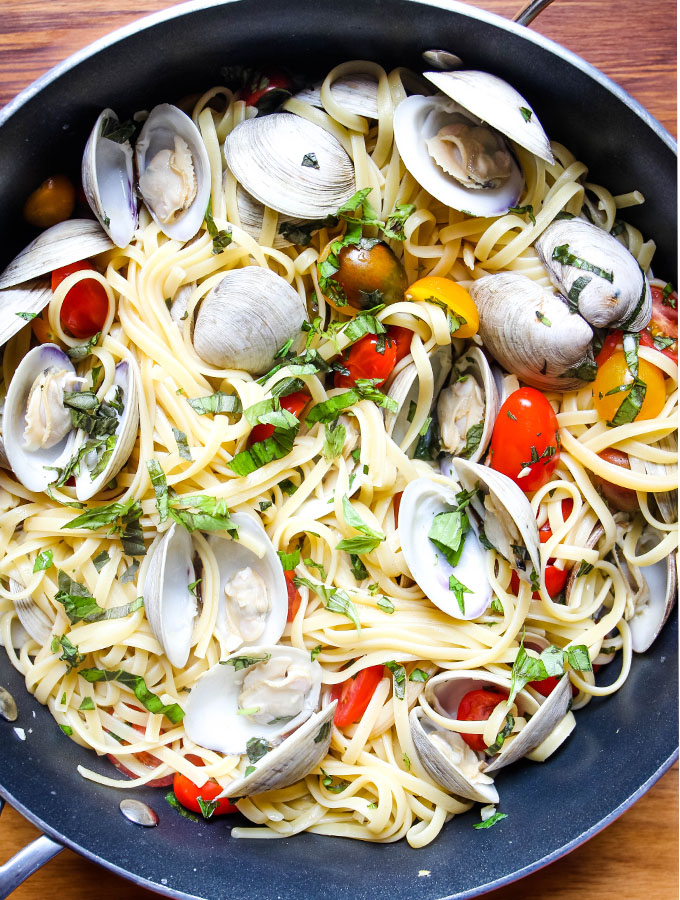 Limguini, clams, basil, cherry tomatoes, and a white wine sauce are tossed together in a pan.