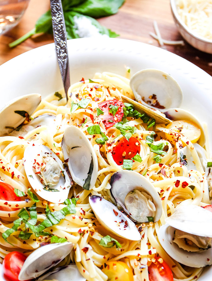 Linguini with clams is plated in a white bowl with a fork and topped with red pepper flakes.