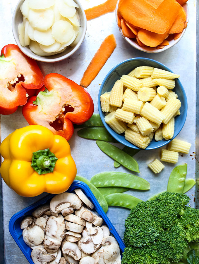 Vegetable stir fry ingredients are displayed individually on a sheet pan.