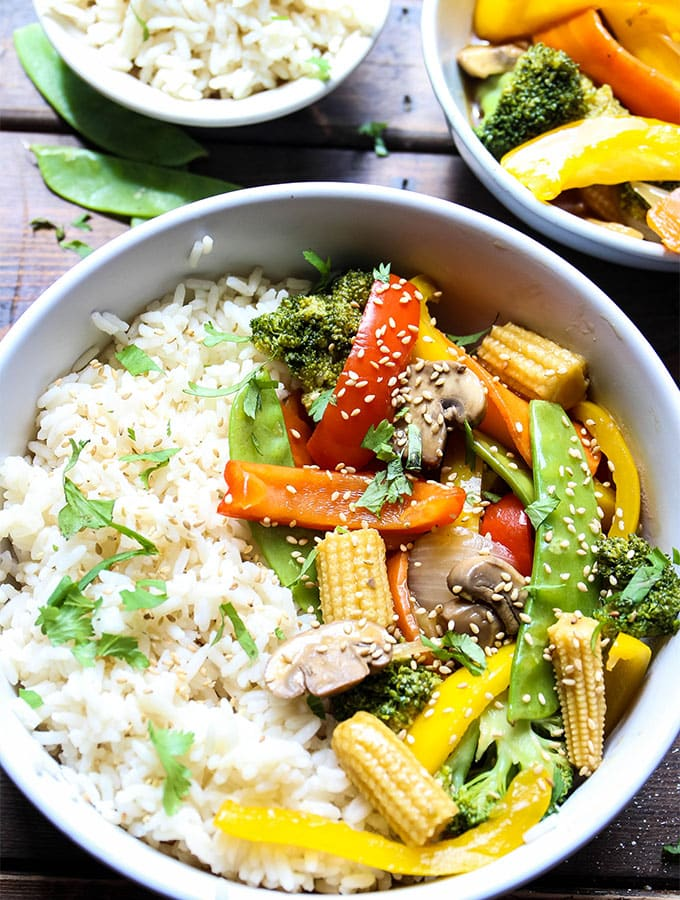 A bowl of stir fry vegetables and white rice is plated next to little bowls of rice and vegetables.