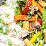 The stir fry vegetables are laid on top of. abed of rice and topped with cilantro and sesame seeds.