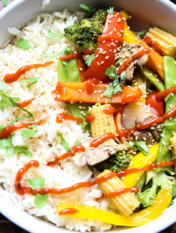 The stir fry vegetables are plated next to white rice and topped with sriracha sauce and sesame seeds in a white bowl.