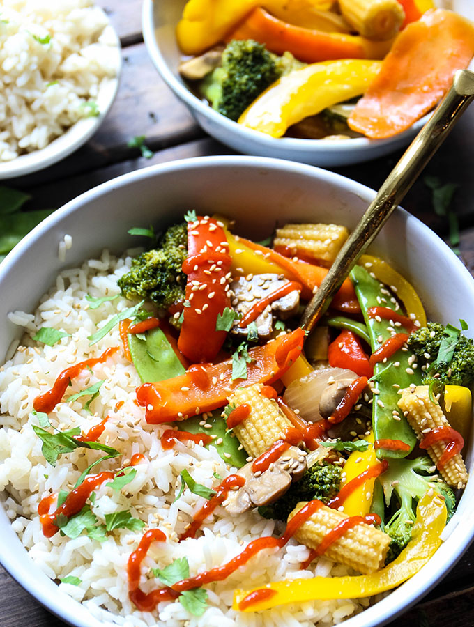The stir fry vegetables are plated in a white bowl with the white rice and topped with sriracha sauce and sesame seeds.