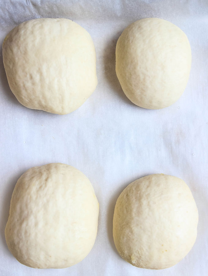 The French bread rolls are shaped and placed on a parchment paper lined baking sheet before baking.