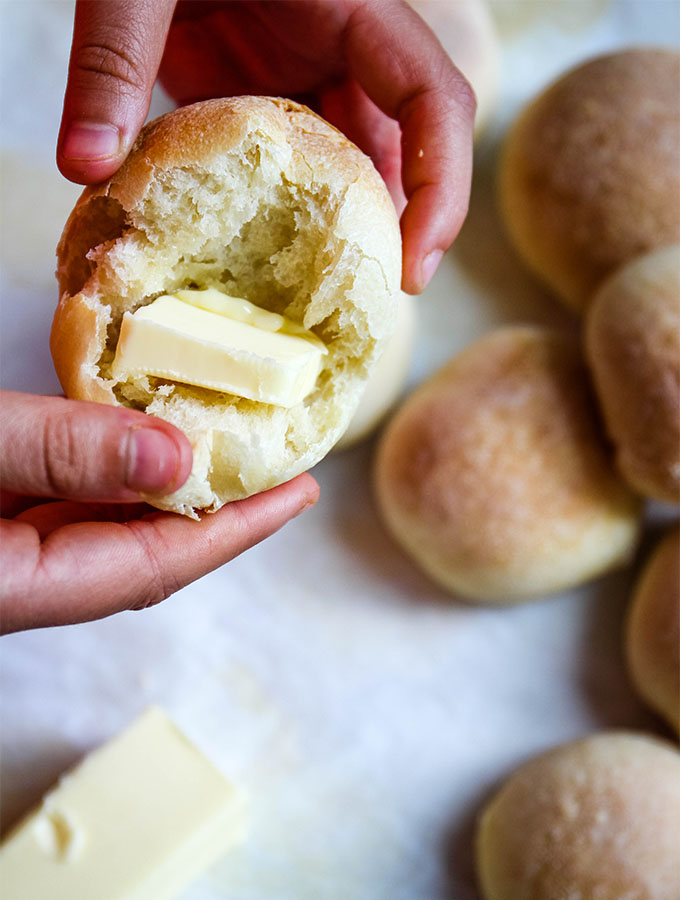 The French bread rolls are broken in half and butter is placed between the bread.