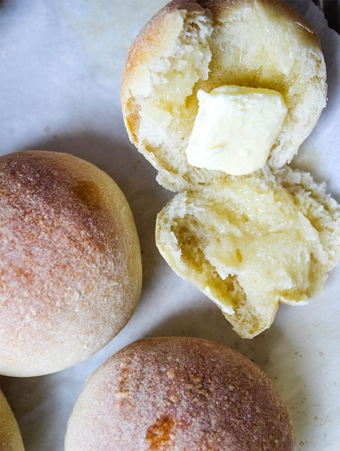 The French rolls are halved and buttered on top of a parchment paper lined baking sheet.