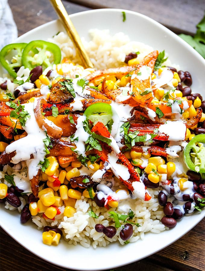 Fajita vegetable bowls are topped with Mexican crema and cilantro for additional flavor and texture.