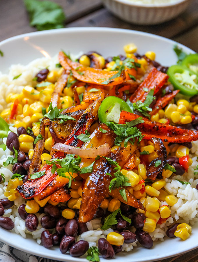 Black beans, corn, fajita seared vegetables, and cilantro is piled on top of rice.
