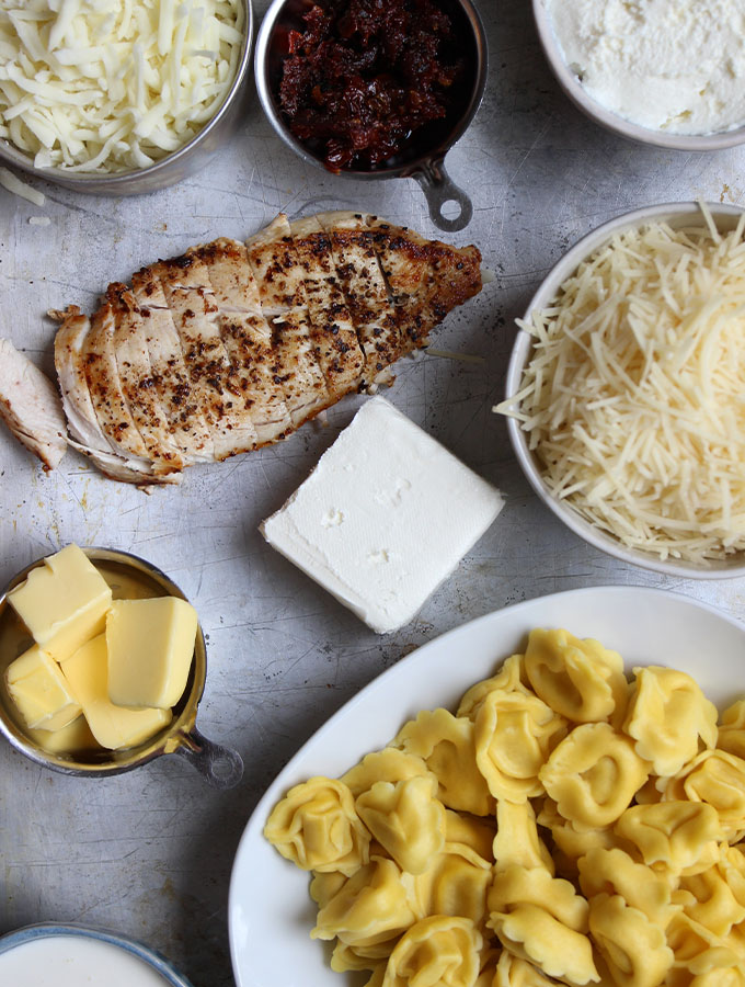 Tortellini bake ingredients are displayed individually on a baking sheet.