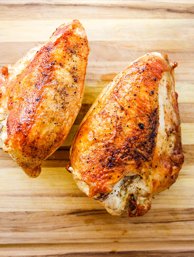 Bone in, skin on chicken breasts are cooked in a pan, then baked for super tender chicken breasts with crispy skin.