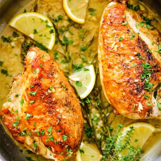 Chicken breasts are placed in the white wine pan sauce and topped with more fresh herbs and lemon wedges.