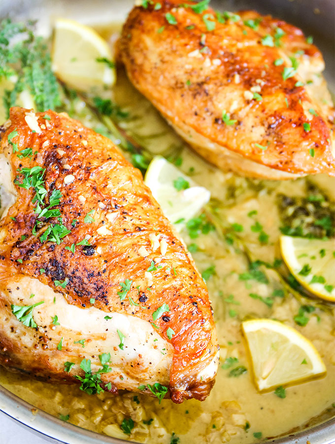 The chicken breasts have crispy, golden brown skin and are placed in the pan with the white wine sauce.