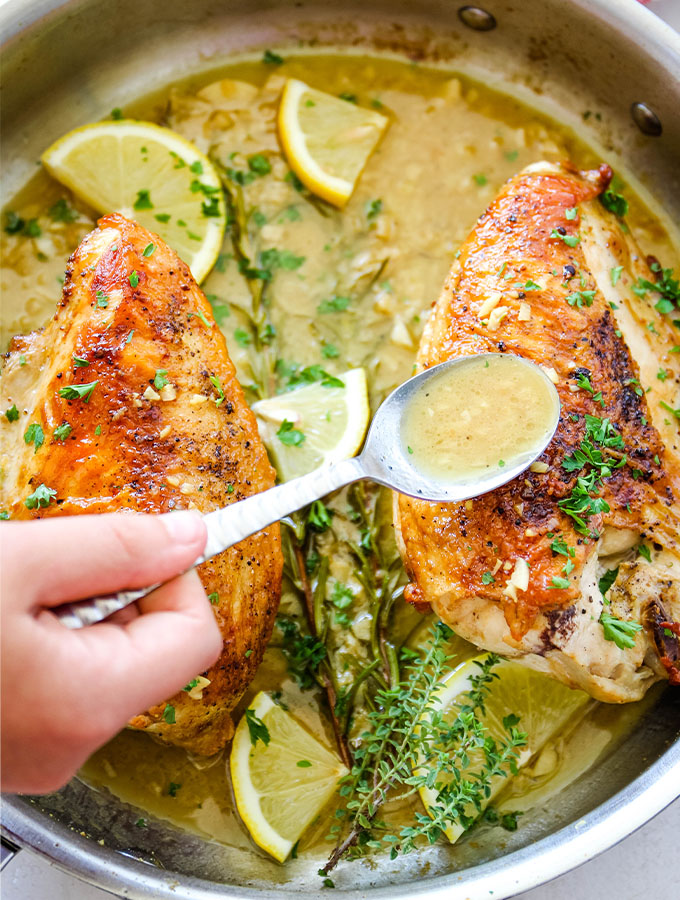 A hand is spooning the white wine pan sauce over the chicken breasts to bast them.