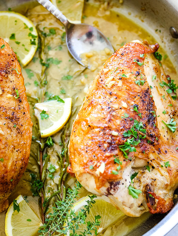 The chicken breasts are placed in the white wine sauce, then topped with fresh parsley, lemon wedges, and fresh herbs.