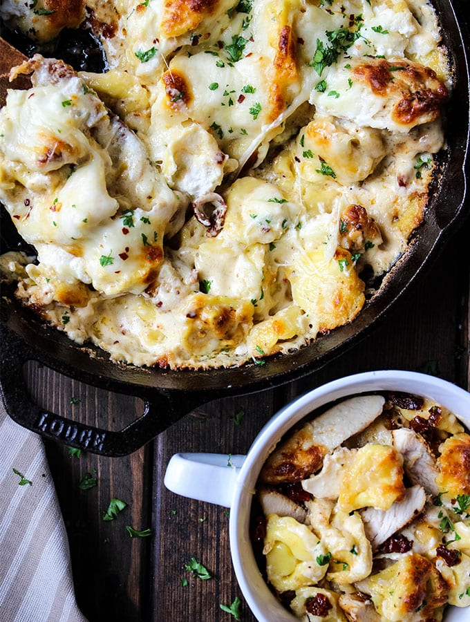 Tortellini bake is baked in a cast iron pan and then plated in a white bowl and topped with chopped parsley.