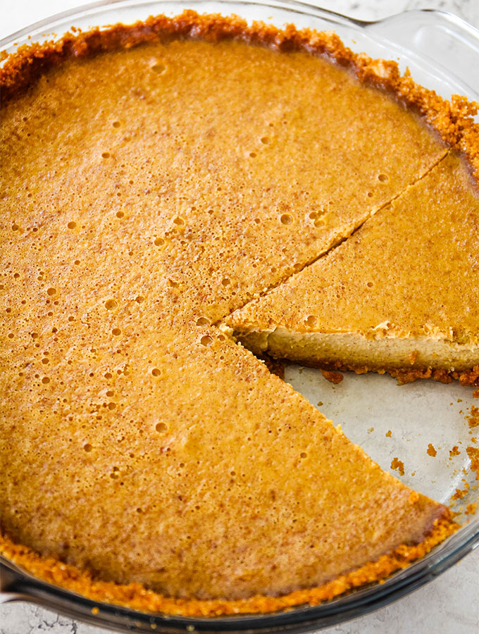Pumpkin pie is cooked in a glass pie dish, cooled, then sliced.