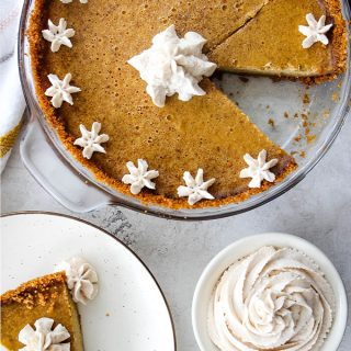 Pumpkin pie is sliced, topped with whipped cream, and a slice is plated on a white plate.